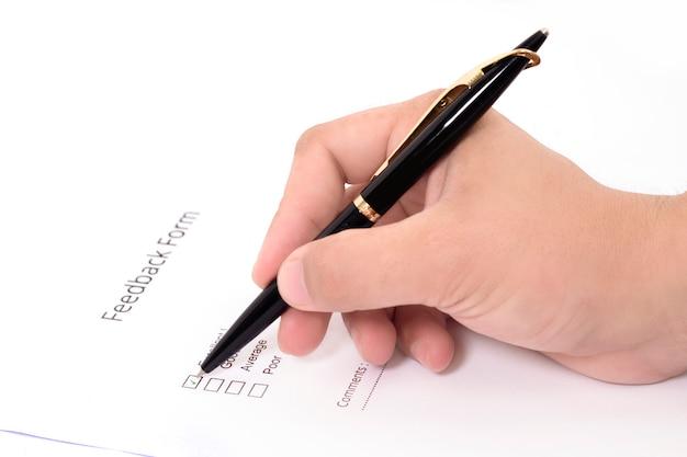 ペンでフィードバックフォームを埋める男の写真。