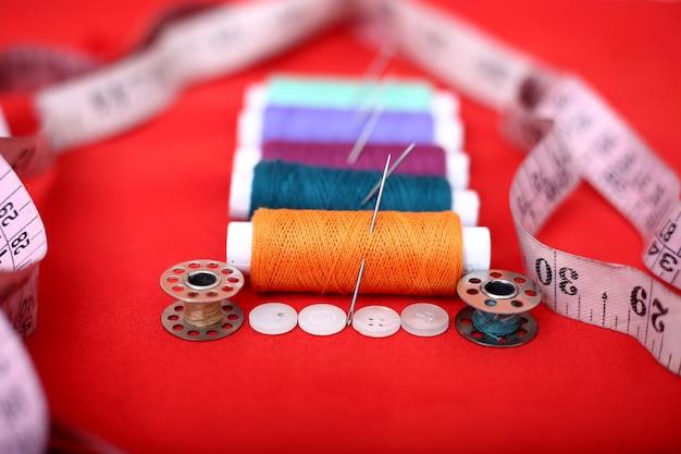 糸、針、ボビン、測定テープ、ボタンの写真。