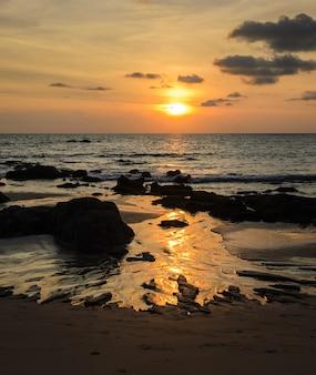 Рок пляж закат с золотым горизонтом