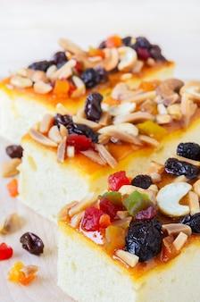 木製のまな板にミックスフルーツとカシューナッツをトッピングしたフルーツケーキ
