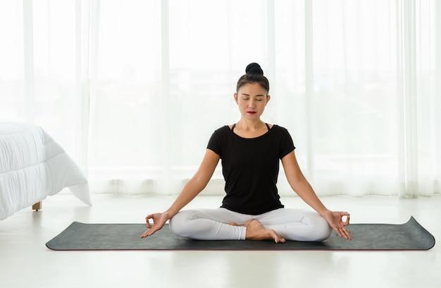 イージーシートポーズまたは白い寝室でムドラとスハサナに座って、自宅でヨガの瞑想の練習をしているアジアの女性。