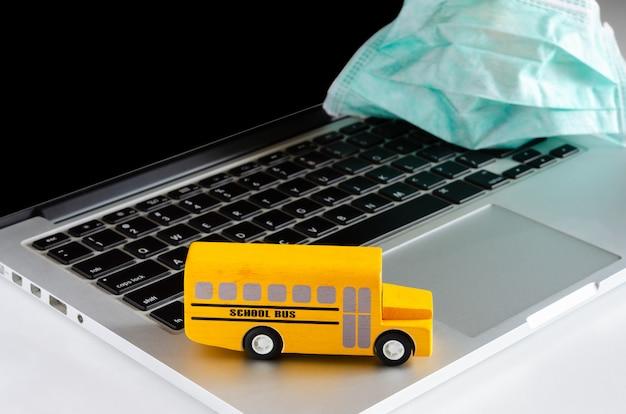 フェイスマスクとラップトップ上の黄色のスクールバス。検疫期間中のオンライン教育とコンセプト
