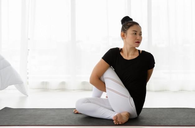ヨガ着席ツイスト運動をしているアジアの女性