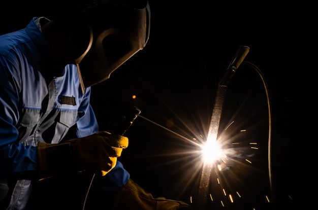 フラックスシールドアーク溶接で金属鋼を溶接する作業員。個人用保護具付き溶接機。
