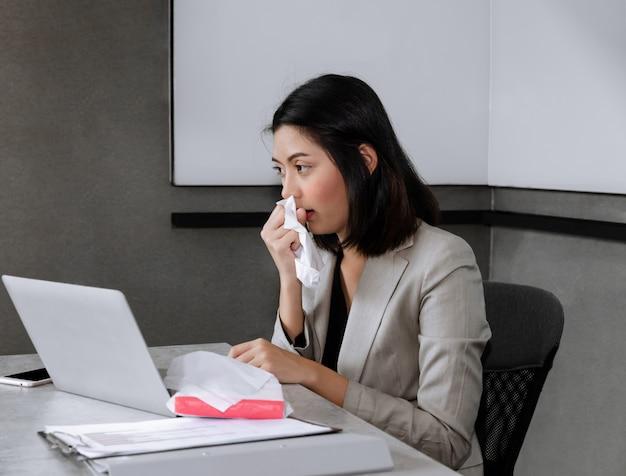 ノートパソコン、くしゃみ、咳でオフィスの机に座っている病気の実業家