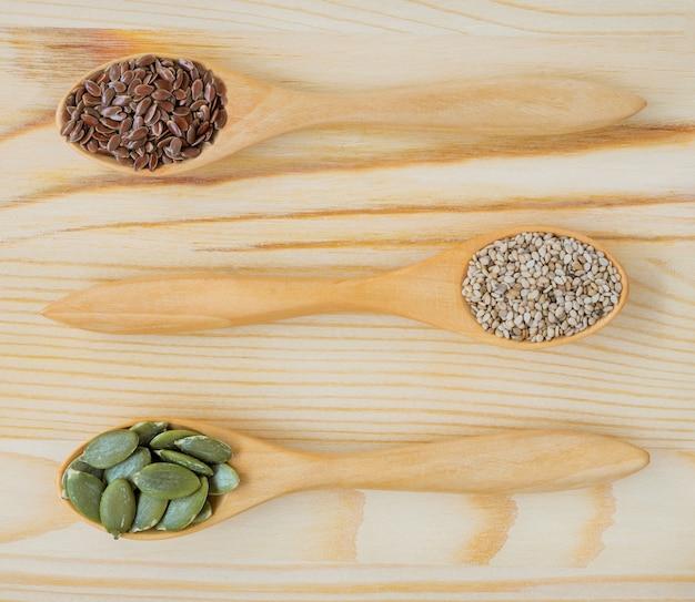 木のスプーンで乾燥亜麻、ゴマ、カボチャの種