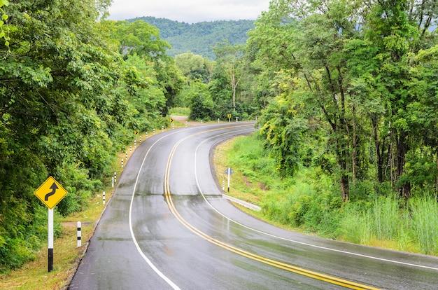 急な逆カーブの前兆の交通標識と雨の後の湿潤な山のアスファルト道路