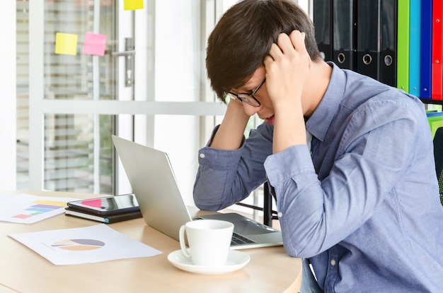 若い欲求不満のアジア系のビジネスマンは彼の仕事で、コントロール不能です。オフィスでの仕事の失敗に対するストレスと頭痛