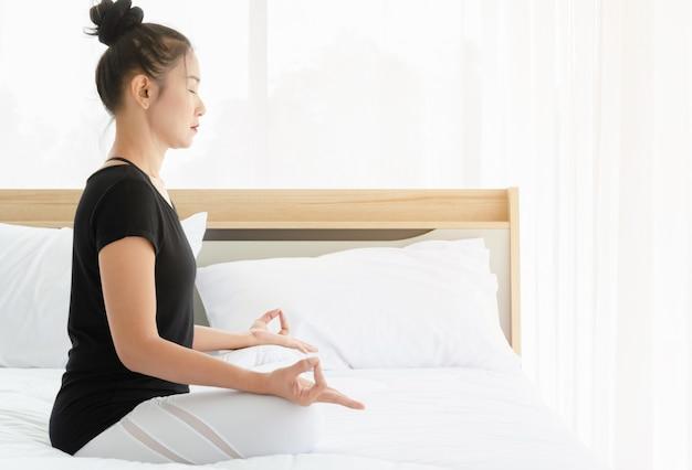 アジアの女性のヨガの練習、寝室のベッドの上のムードラジェスチャーでハーフロータスポーズを行う