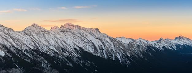 カナダ、アルバータ州バンフ国立公園で見事な雪の夕日がカナダのロッキー山脈を覆った
