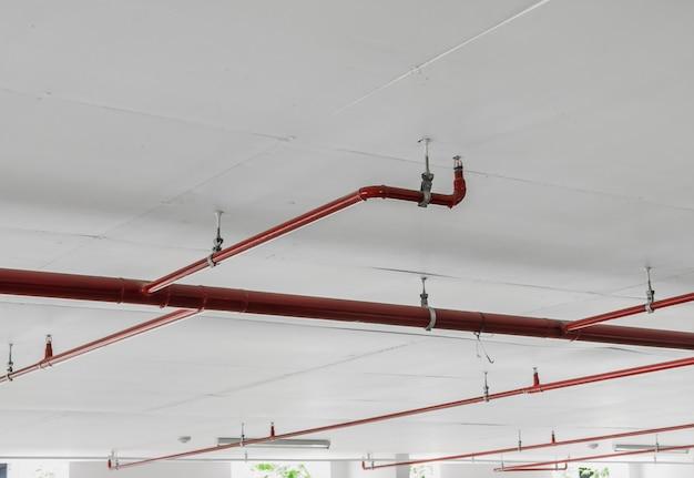 火災スプリンクラーと白い天井の背景に赤いパイプ
