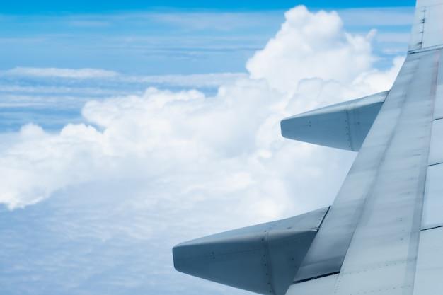 青い空と雲の背景が美しい飛行機の翼、飛行機の窓からの眺め。