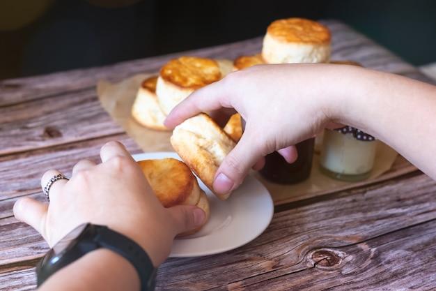 木製のテーブルの白いプレートにクリームチーズと伝統的なイギリスのスコーンを両手