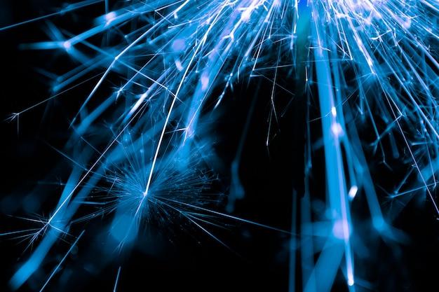 Выборочный фокус светло-голубой сверкающий бенгальский огонь бенгальский огонь на черном фоне.