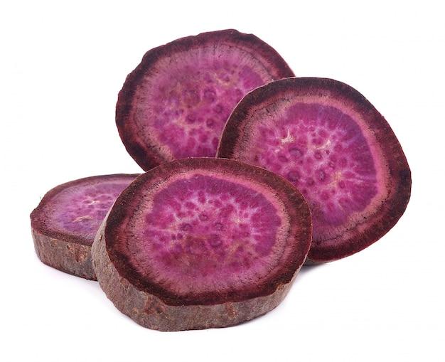 Фиолетовый цветной сладкий картофель на белом фоне