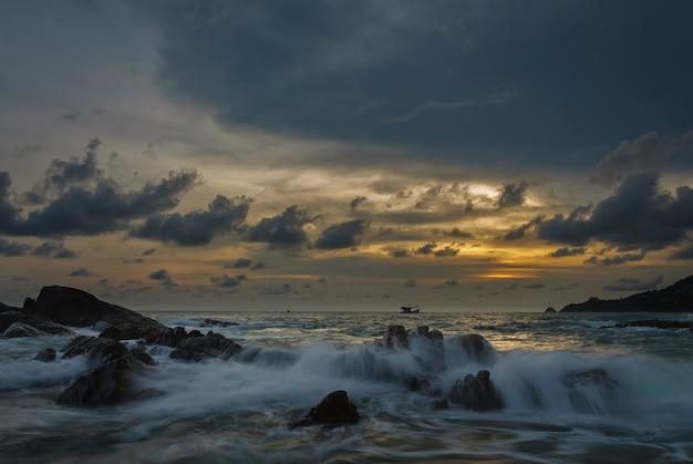 海と石の波の夕日