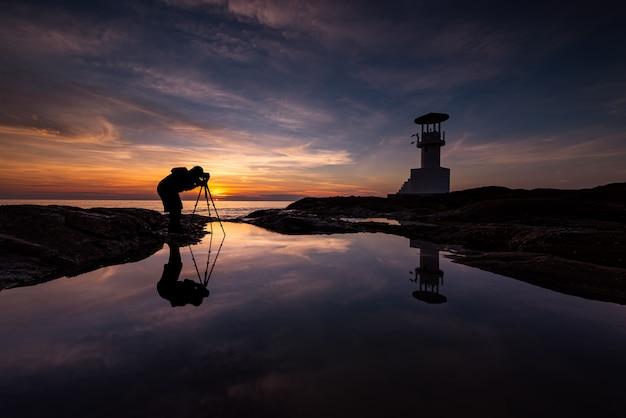 灯台のシルエットカメラマン