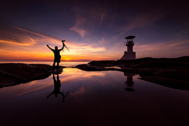 Силуэт фотографа с маяком