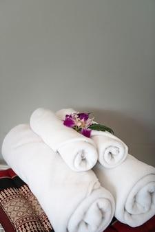Полотенце с орхидеей в интерьере спальни для клиентов отеля.