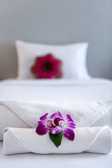 Полотенце с орхидеей на украшение кровати в интерьере спальни для клиентов отеля.