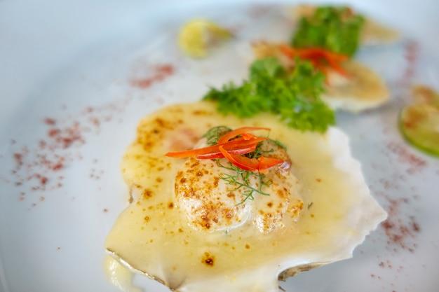 Обжаренные морские гребешки с маслом, чесноком, жареным морским гребешком на белой тарелке.