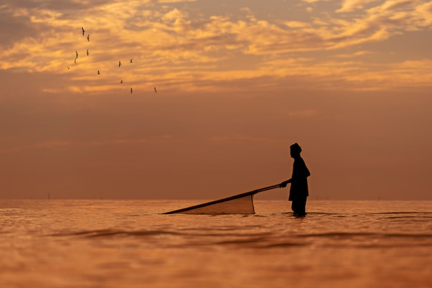 Силуэт местного рыбака, поиск креветок с помощью традиционных сетей на рассвете.