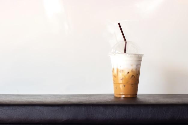 プラスチックカップで氷のカプチーノ。白い背景にコピースペース。リフレッシュメント飲料。