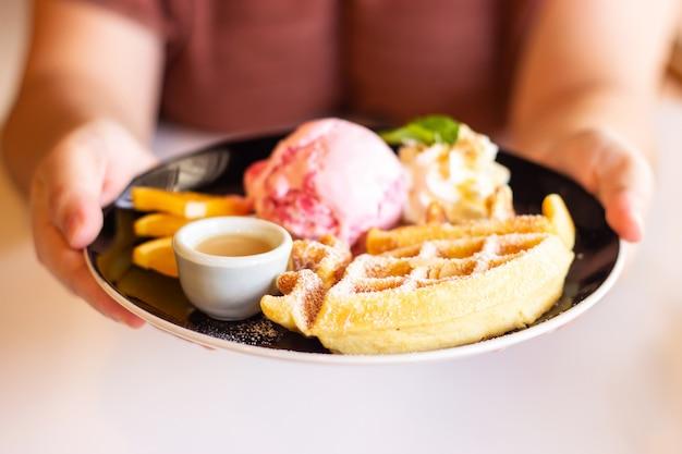 Рука женщины держа плиту самодельной вафли, подается с клубничным мороженым.