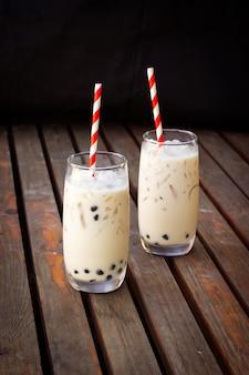 ガラスのミルクティーを泡立たせます。アジアの流行飲料タピオカと甘い飲み物。