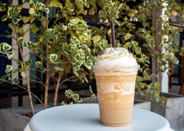 カプチーノをプラスチック製のコップにブレンド。ホイップクリームを添えて。飲み物を飲みます。好きなカフェイン飲料。