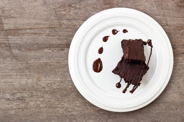 自家製ブラウニーにチョコレートファッジを添えています。木製の背景に甘いデザート。