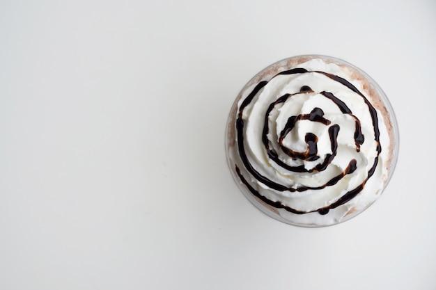プラスチックカップのモカフラッペにホイップクリームの平面図。コピースペースを持つ飲料の背景。