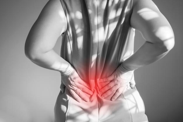 女性は背中の痛みです。ウエストで使用される手のサポート