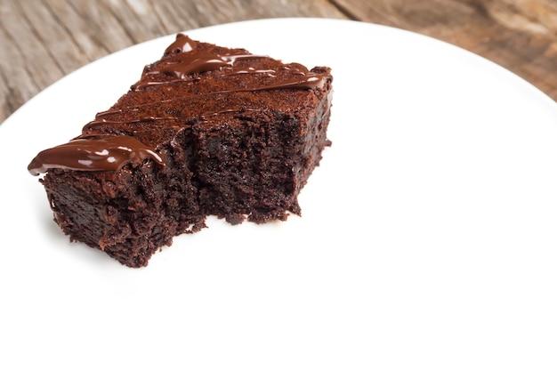 Домашние пирожные на белой тарелке. с шоколадной выдумкой. над деревянным фоном.