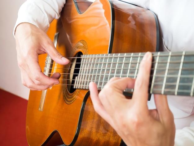 男はギターを弾く。クラシック音楽楽器。弦楽器。