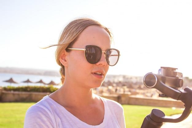 ビデオブロガーの女の子。ジンバルで安定したグリップにアクションカメラを持つオペレーター