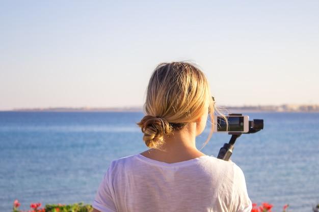ビデオブロガーの女の子。ジンバルで安定したグリップにアクションカメラを持つオペレーター。
