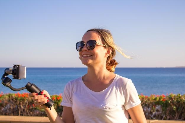 旅行、ジンバルと携帯電話でビデオを作るビデオブロガーの夕日を撮影する女性