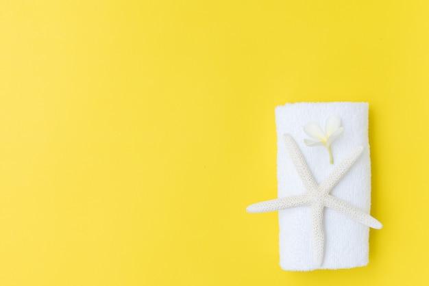 Летняя коллекция, плоская лежащая звезда, белое полотенце и цветок франжипани на желтом фоне