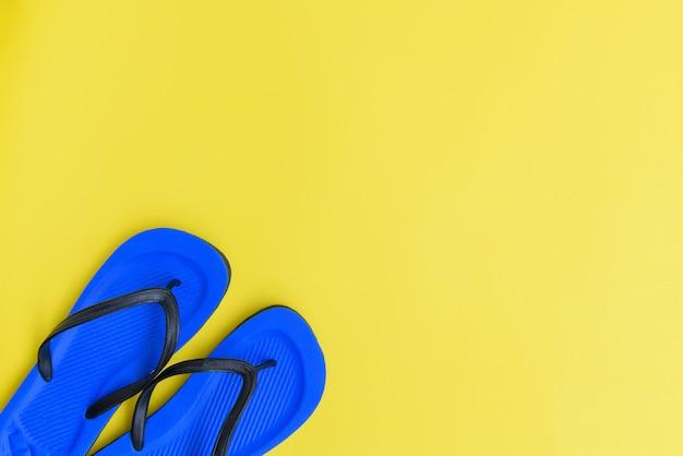 Плоская планировка, пляжные шлепанцы на желтом фоне, вид сверху