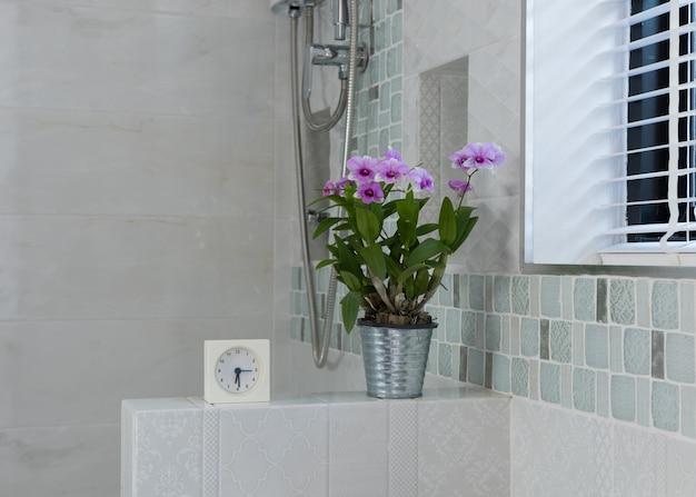 モダンなバスルームのインテリアに目覚まし時計と花の装飾