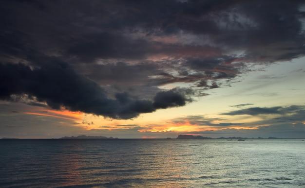 パノラマの劇的な熱帯の海の夕日と雲の雨の背景