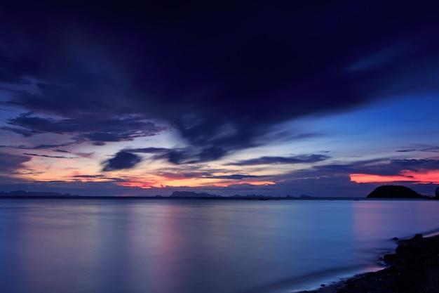 パノラマの劇的な熱帯の青い海の夕日と空の背景