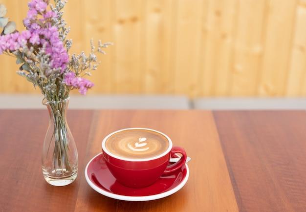 木製のテーブルと花の花瓶の装飾のラテアートと赤のホットコーヒーカップ