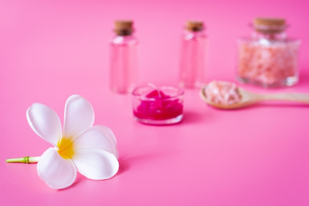 Концепция оздоровительного спа, белый цветок плюмерии, красная свеча, бутылка с жидким мылом из морской соли и розы