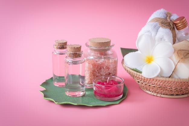 スパヒマラヤ塩、赤いろうそく、牛乳とバラの液体石鹸、白いタオル、ピンクの上の緑の葉に花を設定