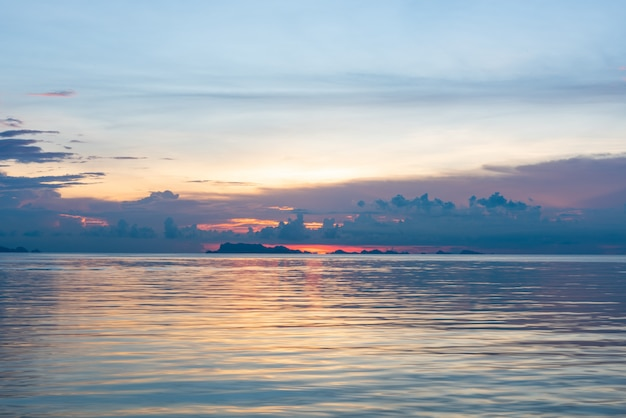 美しい熱帯ピンク青い海の夕日と黄色の雲の背景