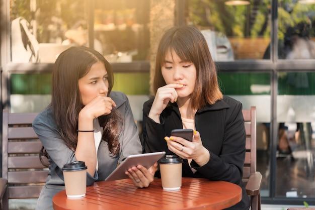 Азиатская красивая деловая женщина работает с планшета и смартфона в кафе кафе