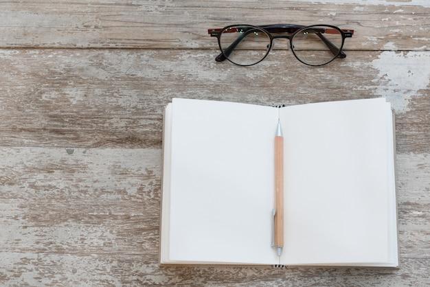 空白のノートブック、鉛筆、眼鏡