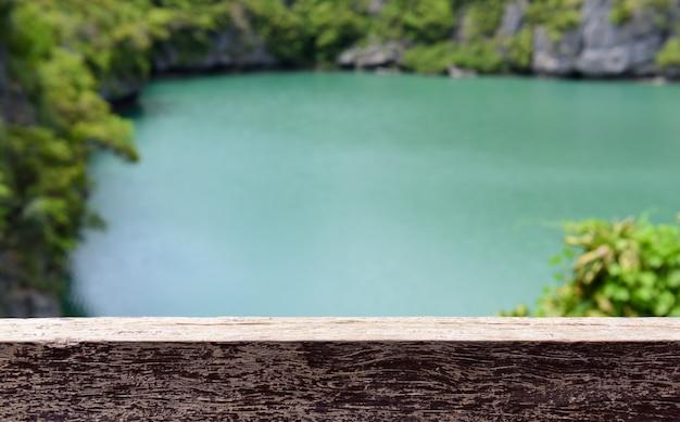 ぼやけた緑の木と緑の湖の上の木の板